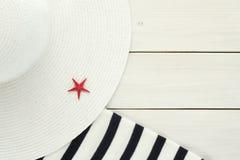 Sombrero de Sun y manta de la playa en el fondo de madera blanco Foto de archivo