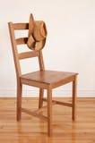 Sombrero de vaquero en una silla de madera Foto de archivo