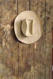 Sombrero de vaquero que cuelga en una pared de madera vieja Imágenes de archivo libres de regalías