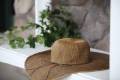Sombrero del algodón de la mujer del verano que se sienta en una repisa de madera blanca imagen de archivo