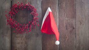 Sombrero del ayudante de Santa Claus aislado y guirnalda hecha a mano de las bayas rojas de la Navidad en la cerca de madera del  Fotografía de archivo libre de regalías