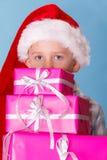 Sombrero del ayudante de santa del niño pequeño con las cajas de regalo rosadas Foto de archivo