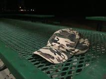 Sombrero del camuflaje en la mesa de picnic del parque Imagen de archivo