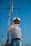 Sombrero del capitán del niño pequeño que lleva feliz y camisa rayada del marinero a bordo del barco recreativo foto de archivo libre de regalías
