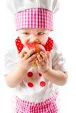 Sombrero del cocinero de la muchacha del cocinero del bebé que lleva con la manzana fresca. Imagen de archivo libre de regalías