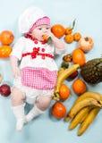 Sombrero del cocinero de la muchacha del cocinero del bebé que lleva con las frutas frescas Fotografía de archivo