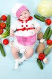 Sombrero del cocinero de la muchacha del cocinero del bebé que lleva con las verduras frescas. Imágenes de archivo libres de regalías