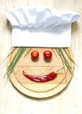 Sombrero del cocinero en concepto de la comida del extracto de la tabla de cortar Foto de archivo
