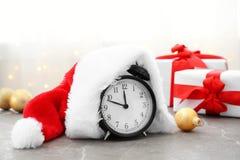 Sombrero del despertador y de Papá Noel en la tabla cuenta de +EPS los días 'hasta la pizarra de la Navidad Fotografía de archivo
