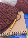 Sombrero del ganchillo de Brown con el gancho, hilados y libros de oro. Fotografía de archivo