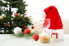 Sombrero del reloj de arena, de Papá Noel y decoración en la tabla cuenta de +EPS los días 'hasta la pizarra de la Navidad Fotos de archivo