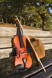 Sombrero del violín y de vaquero en un banco de parque Fotos de archivo libres de regalías
