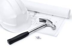 Sombrero duro, martillo, clavos y druft blancos Imagen de archivo libre de regalías
