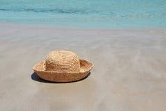 Sombrero en la arena por el mar Imagen de archivo