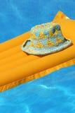 Sombrero en la naranja airbed foto de archivo libre de regalías