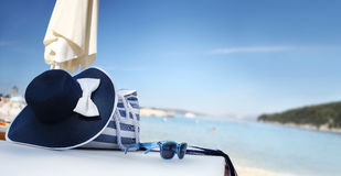 Sombrero en la playa con el bolso, las gafas de sol y la toalla Imagen de archivo libre de regalías