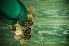 Sombrero feliz del duende del día del St Patricks con las monedas de oro en fondo de madera verde del vintage fotos de archivo