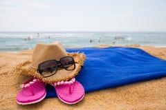 Sombrero, gafas de sol y otros artículos en una playa Imagen de archivo
