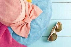 Sombrero hermoso del verano con las gafas de sol en fondo de madera azul Imagen de archivo