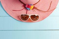 Sombrero hermoso del verano con las gafas de sol en fondo de madera azul Imagenes de archivo