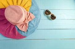 Sombrero hermoso del verano con las gafas de sol en fondo de madera azul Fotos de archivo libres de regalías