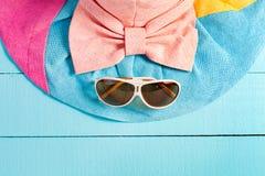 Sombrero hermoso del verano con las gafas de sol en fondo de madera azul Fotografía de archivo