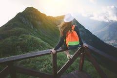 Sombrero joven y mochila que llevan de la mujer que viajan que se sientan arriba en el top de la montaña con el pelo que agita, i Foto de archivo libre de regalías