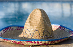 Sombrero laying beside swimming pool. A traditional Mexican sombrero laying beside swimming pool Stock Photography