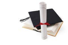 Sombrero, libro y diploma de la graduación Fotos de archivo libres de regalías