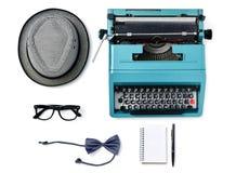 Sombrero, máquina de escribir, lentes, corbata de lazo, cuaderno y pluma Imagen de archivo