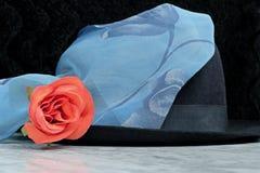 Sombrero negro con una bufanda azul con el adorno de la rosa roja de las rosas en una tabla de mármol Imágenes de archivo libres de regalías