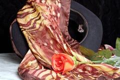 Sombrero negro con una bufanda con un adorno del tigre de la rosa del rojo en una tabla de mármol Imagen de archivo