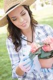 Sombrero que lleva bastante joven de la mujer adulta que cultiva un huerto al aire libre Foto de archivo libre de regalías