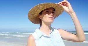 Sombrero que lleva de la mujer hermosa mientras que camina en la playa almacen de metraje de vídeo