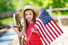 Sombrero que lleva de la niña adorable que sostiene la bandera americana al aire libre en día de verano hermoso Fotografía de archivo libre de regalías