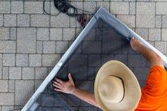 Sombrero que lleva del hombre que repara la puerta vieja del patio foto de archivo