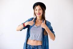 Sombrero que lleva del retrato de la mujer joven que muestra los pulgares para arriba Fotografía de archivo