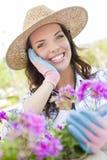 Sombrero que lleva hermoso de la mujer joven que cultiva un huerto al aire libre Foto de archivo