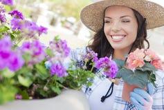 Sombrero que lleva joven de la mujer adulta que cultiva un huerto al aire libre Fotografía de archivo