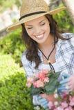 Sombrero que lleva joven de la mujer adulta que cultiva un huerto al aire libre Fotos de archivo