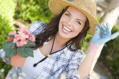 Sombrero que lleva joven de la mujer adulta que cultiva un huerto al aire libre Imagenes de archivo