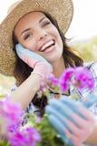 Sombrero que lleva joven de la mujer adulta que cultiva un huerto al aire libre Imagen de archivo