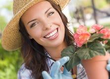 Sombrero que lleva joven de la mujer adulta que cultiva un huerto al aire libre Foto de archivo libre de regalías