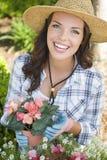 Sombrero que lleva joven sonriente de la mujer adulta que cultiva un huerto al aire libre Foto de archivo libre de regalías