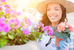 Sombrero que lleva joven y guantes de la mujer adulta que cultivan un huerto al aire libre Imágenes de archivo libres de regalías