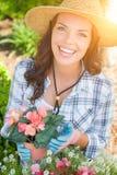 Sombrero que lleva joven y guantes de la mujer adulta que cultivan un huerto al aire libre Imagen de archivo libre de regalías