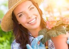 Sombrero que lleva joven y guantes de la mujer adulta que cultivan un huerto al aire libre Fotografía de archivo