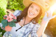Sombrero que lleva joven y guantes de la mujer adulta que cultivan un huerto al aire libre Foto de archivo