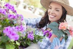 Sombrero que lleva sonriente de la mujer joven que cultiva un huerto al aire libre Fotografía de archivo