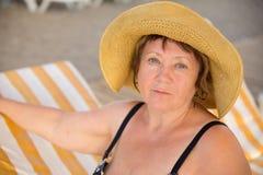 Sombrero que lleva sonriente de la mujer mayor en la playa en sunbed Imagen de archivo